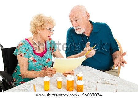 Senior couple at the dining room table discussing medical and prescription costs.  White background.