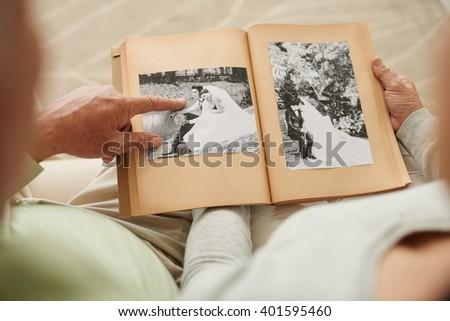 Senior couple at their wedding photos in photo album - stock photo