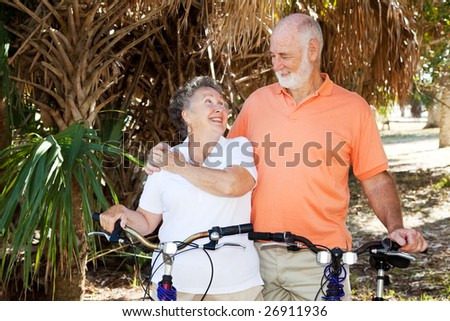 Senior couple bicycling together in the park. - stock photo