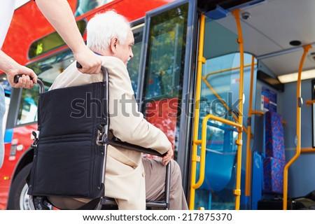 Senior Couple Boarding Bus Using Wheelchair Access Ramp - stock photo