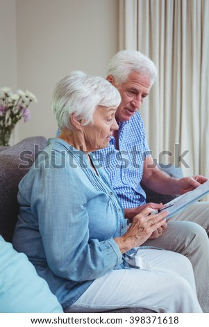 Senior couple calculating bills while sitting on sofa at home - stock photo