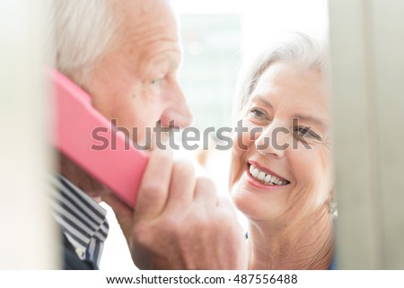 Senior couple call in a phone box