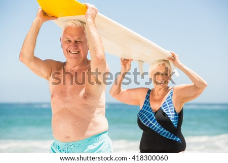 Senior couple carrying a surfboard on a sunny day - stock photo