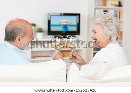 Senior couple celebrating with white wine clinking their glasses and toasting each other with a laugh as they sit on a sofa in their living room watching television - stock photo