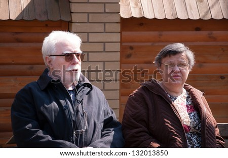 Senior couple chatting on a park bench - stock photo