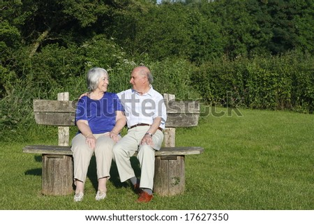 Senior couple chatting on a park bench on a summers evening.