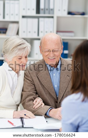 Senior couple chatting to a business broker in an office as they receive financial planning advice for their retirement - stock photo