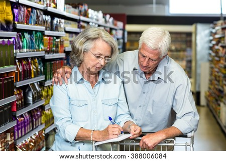 Senior couple checking list at the supermarket