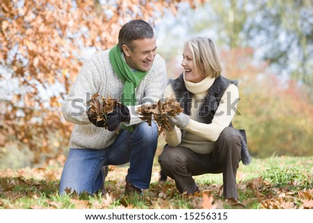 Senior couple collecting autumn leaves together - stock photo