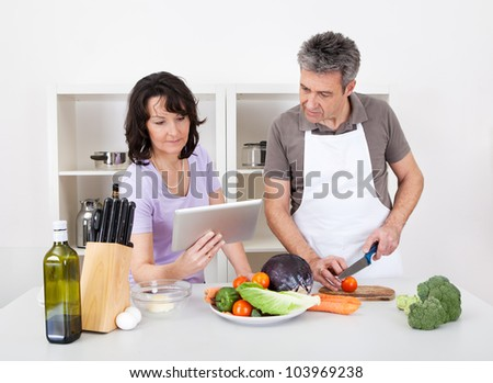 Senior couple cooking lunch at home. Isolated on white - stock photo