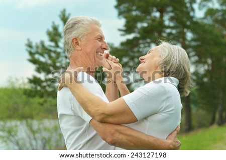 Senior couple dancing near lake - stock photo