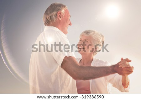 Senior couple dancing on the beach against light beam - stock photo