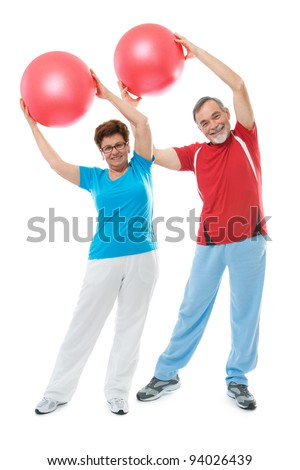 Senior couple doing fitness exercise with a ball at sport gym - stock photo