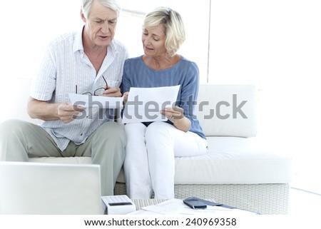 Senior couple doing home finances - stock photo