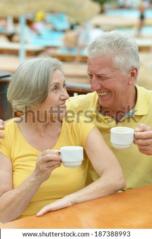 Senior couple drinking coffee outside at the resort during vacation