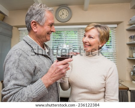 Senior couple drinking red wine at home in the kitchen - stock photo