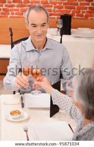 Senior couple drinking rose in a restaurant - stock photo