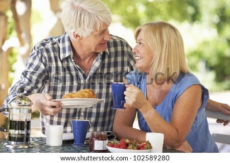 Senior couple eating breakfast outdoors - stock photo