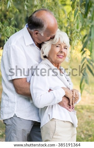 Senior couple embracing and kissing in the park