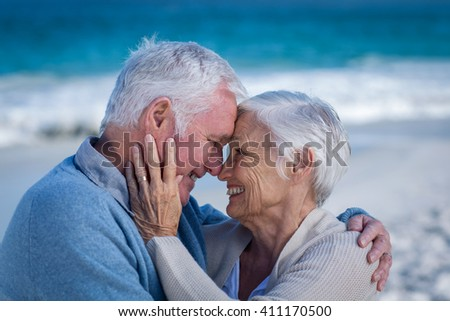 Senior couple embracing at the beach - stock photo