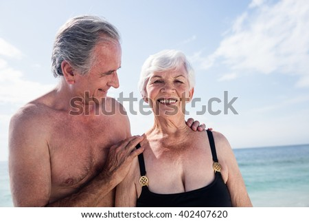 Senior couple embracing on beach at a sunny day - stock photo