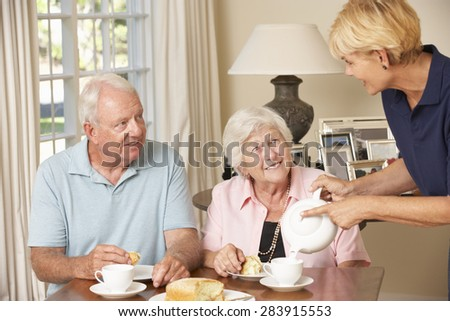 Senior Couple Enjoying Afternoon Tea Together At Home With Home Help
