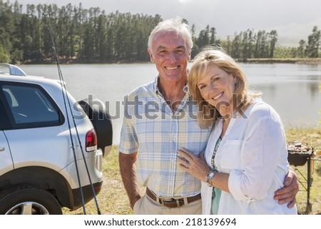 Senior Couple Enjoying Barbeque By Lake - stock photo