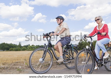 senior couple enjoying bike trip - stock photo