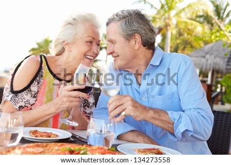 Senior Couple Enjoying Meal In Outdoor Restaurant - stock photo