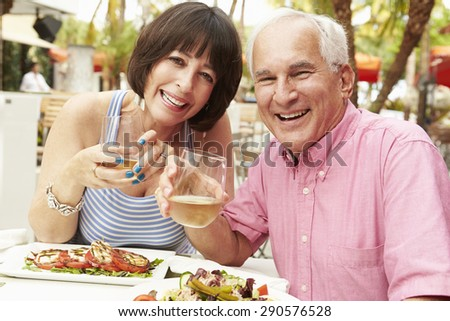 Senior Couple Enjoying Meal In Outdoor Restaurant Together - stock photo
