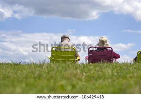 Senior couple enjoying retirement - relaxing in the park against a clear blue sky.