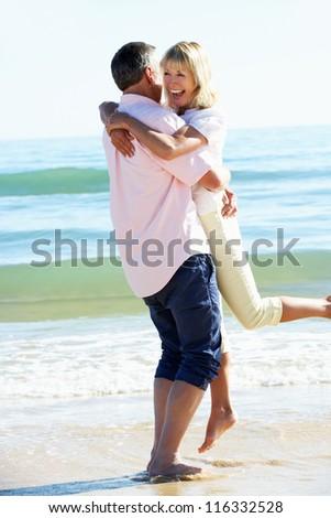 Senior Couple Enjoying Romantic Beach Holiday - stock photo