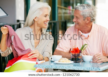Senior Couple Enjoying Snack At Outdoor Cafe After Shopping - stock photo