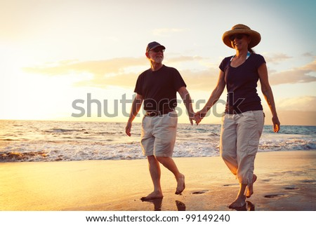 Senior Couple Enjoying Sunset at the Beach - stock photo