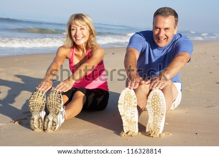 Senior Couple Exercising On Beach - stock photo