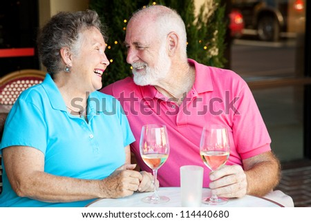 Senior couple flirting and laughing together over a glass of white wine. - stock photo