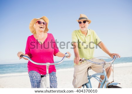 Senior couple going for a bike ride on the beach - stock photo