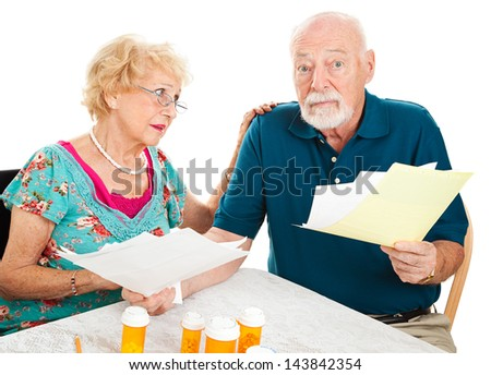 Senior couple going over their medical bills.  They are confused and overwhelmed.  White background. - stock photo