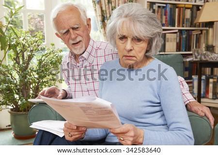 Senior Couple Going Through Finances Looking Worried - stock photo