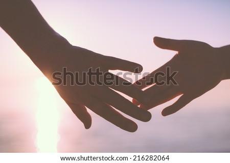 Senior couple hands reach silhouette - stock photo