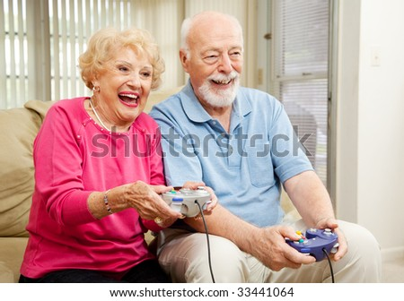 Senior couple has fun at home playing video games together. - stock photo