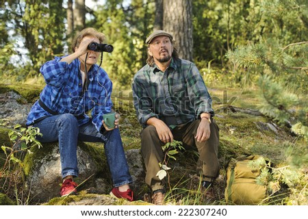 Senior couple have a tea or coffee break in the forest while hiking. They use  binoculars to check out the landscape