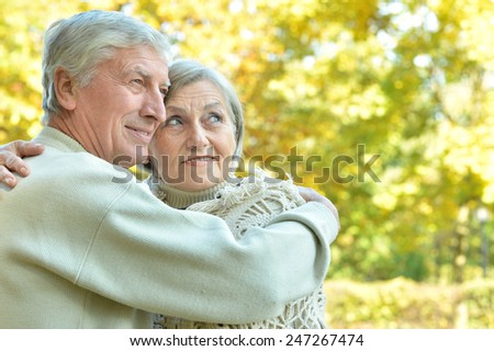 Senior couple have a walk in autumn forest - stock photo