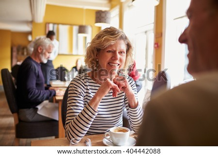 Senior couple have coffee at restaurant, over shoulder view