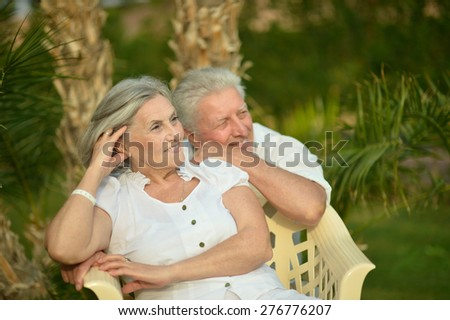Senior couple have fun at tropic hotel garden