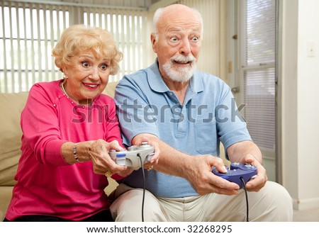 Senior couple having a great time playing video games. - stock photo