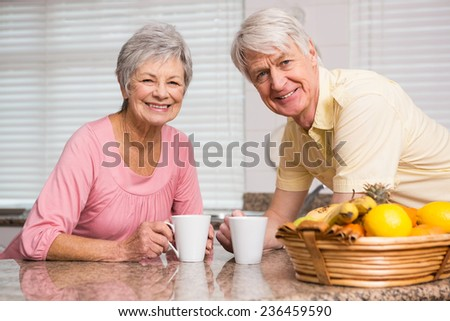 Senior couple having coffee together at home in the kitchen - stock photo