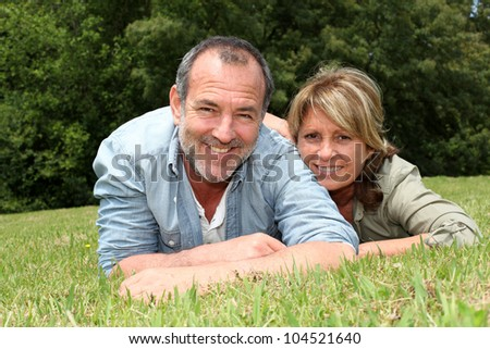 Senior couple having fun laying in grass - stock photo