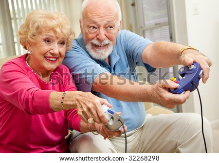 Senior couple having fun playing video games. - stock photo