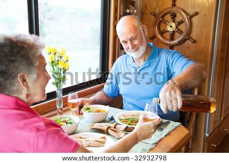 Senior couple having romantic dinner in their motor home. - stock photo